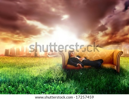 a business man on the sofa in countryside - stock photo