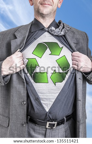 A business man opens his shirt to show off his recycle concept. - stock photo
