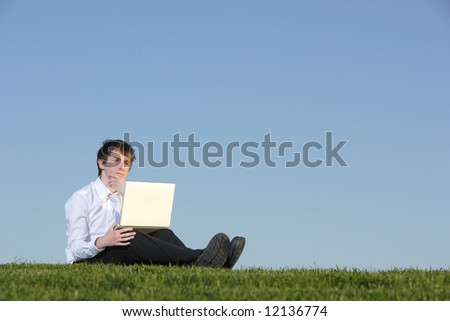 A business man out of the office in a field on a laptop
