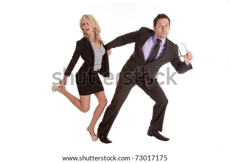 A business man pulling on his business woman's hand running while she is trying to fix her shoe.