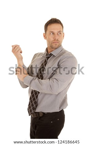 A business man rolling up his sleeves with a serious expression on his face. - stock photo