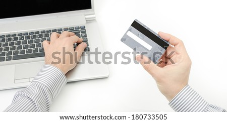 A business man securing a credit card to prevent on line bank account from being hacked - stock photo