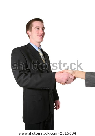 A business man shaking hands with a woman before the start of a meeting