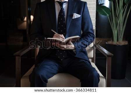 A business man sitting a chair in a lobby - stock photo