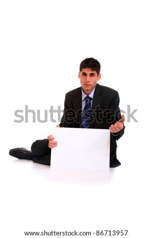 A business man sitting and begging holding an empty sign - stock photo