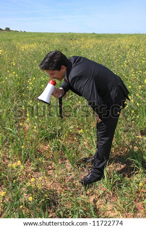 A business man speaking to the plants with a megaphone - stock photo