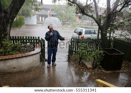 A business man stands outside in the pouring rain wearing a blue rain coat and a clear umbrella waiting for someone or the rain to stop.