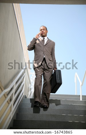 a business man talks on his cell phone as he walks down stairs - stock photo