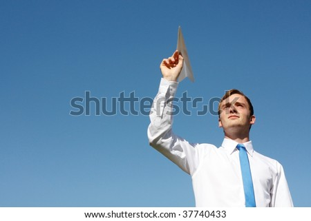 A business man throwing a paper plane - stock photo