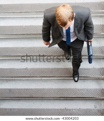 A business man walking down some steps - stock photo