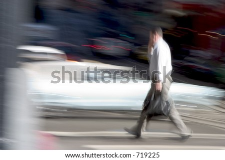 A business man walks across the street briskly while talking on a cell phone.  An intensionally long shutter gives a blurred sense of urgency to the scene.