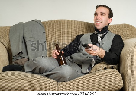 A business man watching some tv and enjoying his beer, after a hard day at work - stock photo
