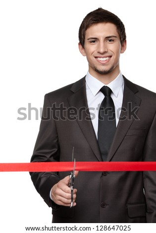 A business man wearing a suit cutting a red ribbon with a pair of scissors. Grand opening ceremony or event, isolated on white - stock photo