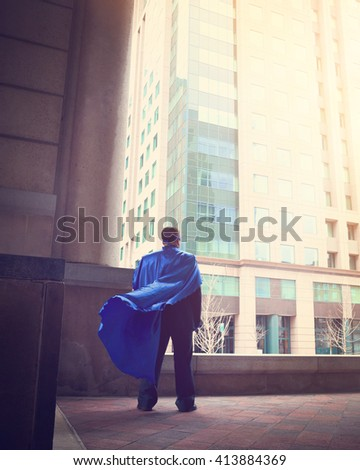 A business man wearing a super cape is standing in a city for a success, strength or power career concept. - stock photo
