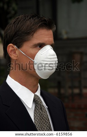 a business man wears a medical face mask or dust mask to protect himself and others from the flu and other airborn virus - stock photo