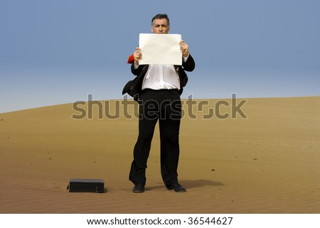 a business man with a briefcase and a notice , alone, on a desert - stock photo