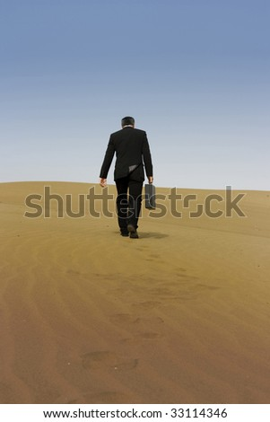 a business man with a briefcase walking alone on a desert - stock photo