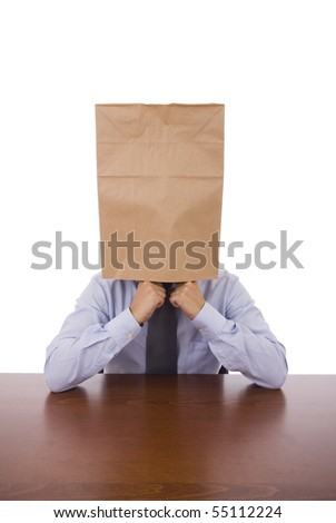 A business man with a cardboard bah on his head - stock photo