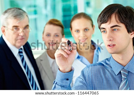 A business man with a highlighter presenting something to his colleagues - stock photo