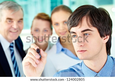A business man with a highlighter ready to draw something for his colleagues - stock photo