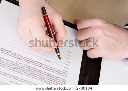 A business man with a red and black pen about to sign a document