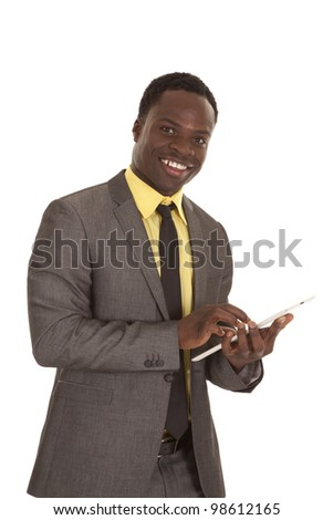 a business man with a smile on his face working on his tablet. - stock photo