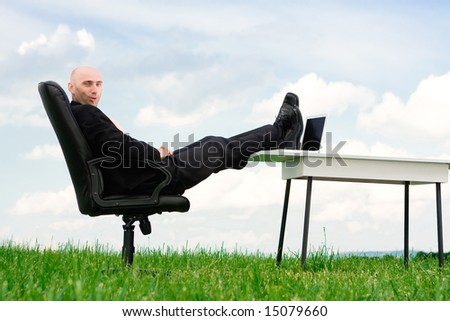 A business man with his feet up on a desk outside. - stock photo