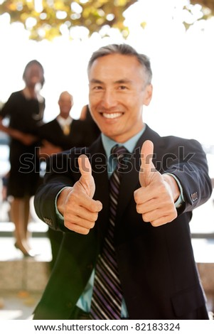 A business man with thumbs up - critical focus on the thumbs - stock photo