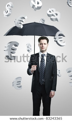 a business man with umbrella under evro and dollar signs rain - stock photo