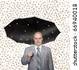 a business man with umbrella under money rain - stock photo
