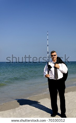 A business man with white shirt and tie holding a fishing pole at the ocean.