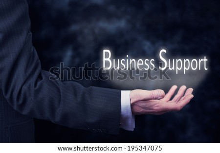 """A business mans hand holding the words, """"Business Support"""". - stock photo"""