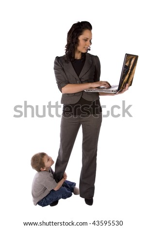 A business mom trying to work while her son hangs on her leg. - stock photo