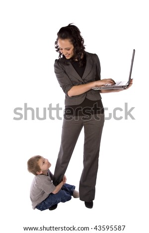 A business mom trying to work while her son hangs on her leg while they smile at eachother.