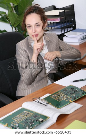 A business sales woman requesting silence while on the phone - stock photo