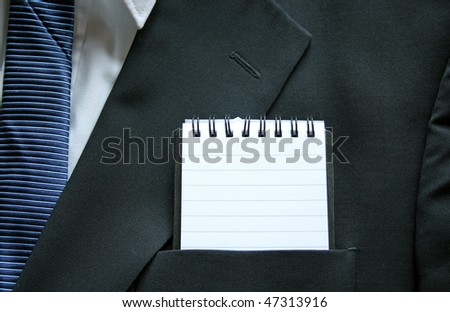 A business suit top pocket with a clear lined notepad - stock photo