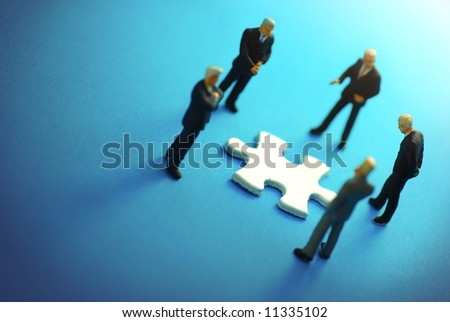 A business team around a puzzle piece. - stock photo