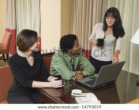A business team cheerfully review good results on their laptop computer in a hotel room during a business trip. - stock photo