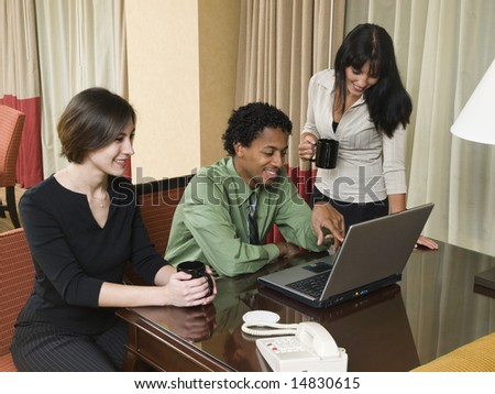 A business team cheerfully review good results on their laptop computer in a hotel room during a business trip.