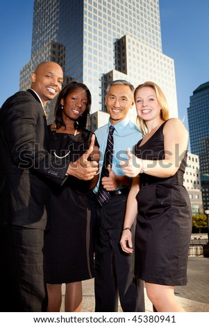 A business team giving a thumbs up - stock photo