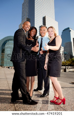 A business team giving a thumbs up showing success - stock photo