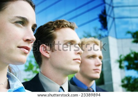 A Business Team looks forward as they stand together in unity outside against a blue business building - stock photo