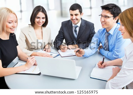 A business team of five plan work in office - stock photo