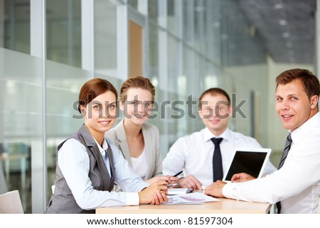 A business team of four sitting at table and looking at camera - stock photo