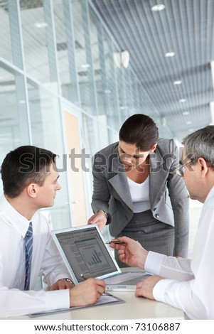 A business team of three planning work in office - stock photo