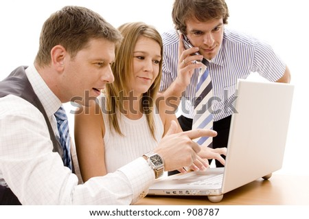 A business team of three works on a laptop computer
