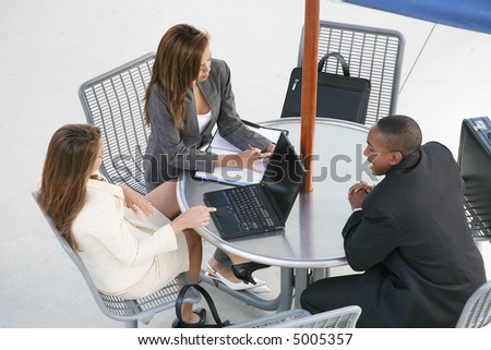 A business team of two women and a man at a table - stock photo