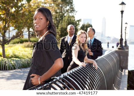 A business team outside - sharp focus on front woman - stock photo