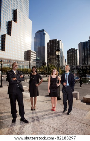 A business team portrait with large buildings in the background - stock photo