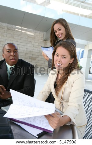A business tean of two women and a man discussing a project - stock photo
